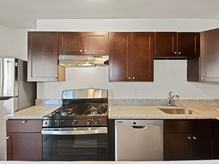 Kitchen with new black appliances and dark brown cabinets