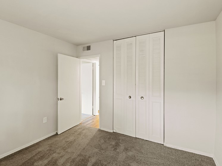Carpeted bedroom with large closet