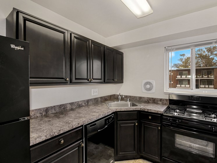 Kitchen with a refridgerator, gas stove and dark cabinets
