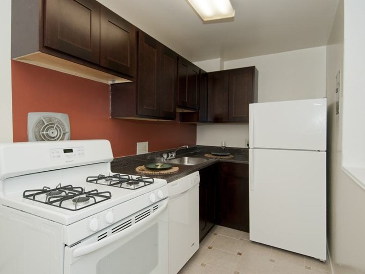Kitchen with dark cabinets and white appliances