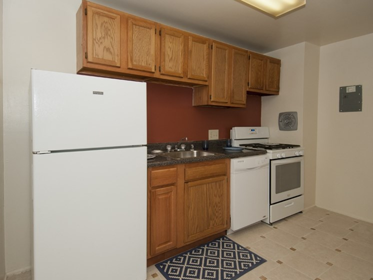 Kitchen with light brown cabinets and white appliances