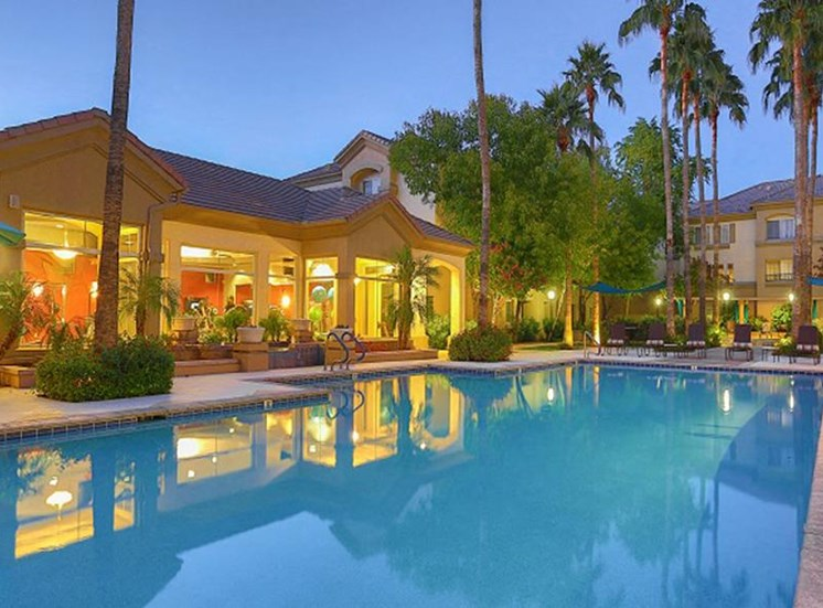 Outdoor pool with lounge seating at night close up
