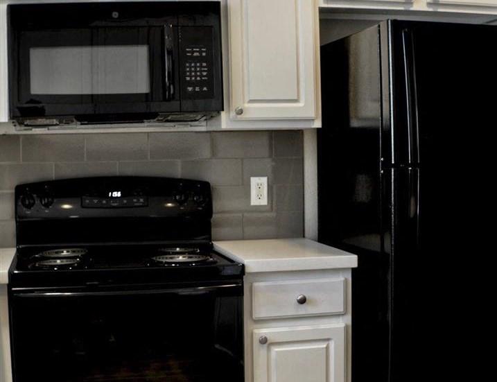 Vacant apartment home kitchen black appliances close up