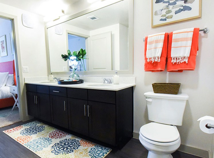 Bathroom model with dual sinks and view of connecting bedroom