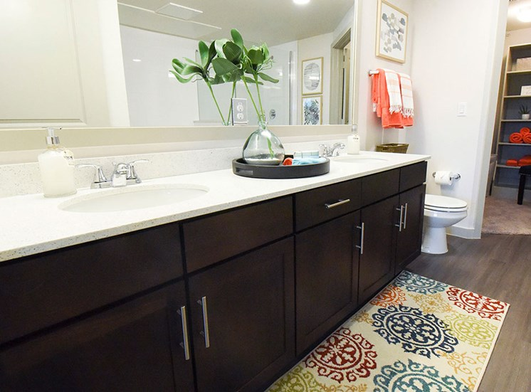 Bathroom model with dual sinks and view of walk in closet
