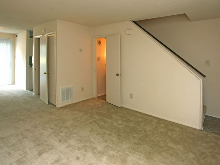 Unfinished living room with view of stairs, half bath, dining room and hall closets