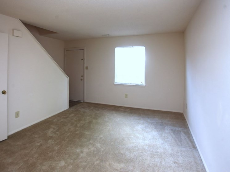 Unfinished Living Room with window, stairs, front door and half bath