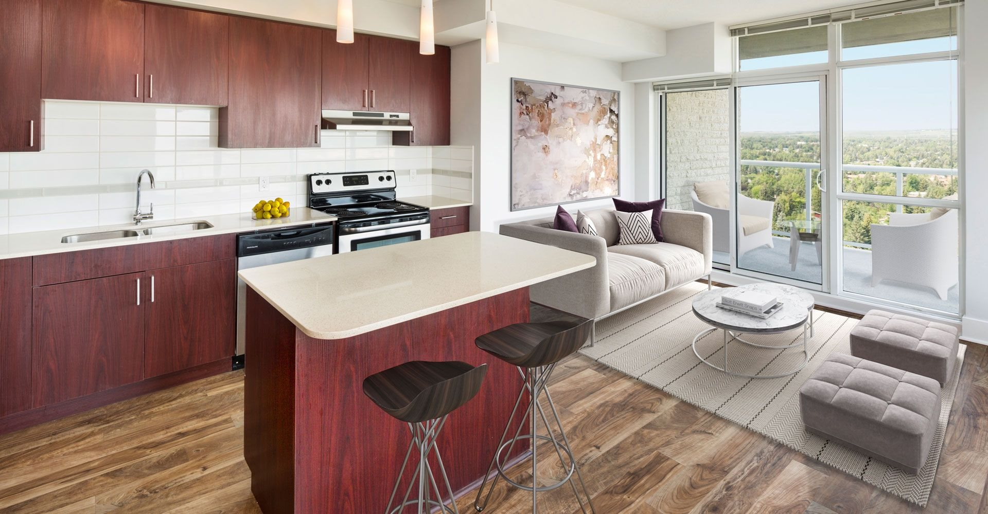 Open concept kitchen with an island, stools, and living room with  a couch and table.
