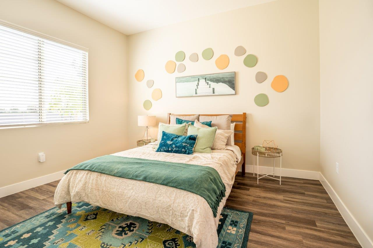 Model bedroom is furnished with a large bed and 2 nightstands at Village Greens of Queen Creek