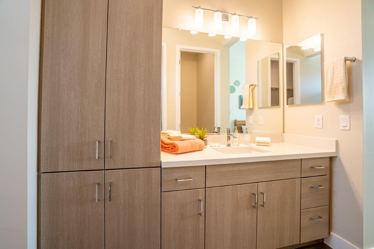 Custom vanity with floor to ceiling cupboards and a large counter sink with storage below in an apartment at Village Greens of Queen Creek