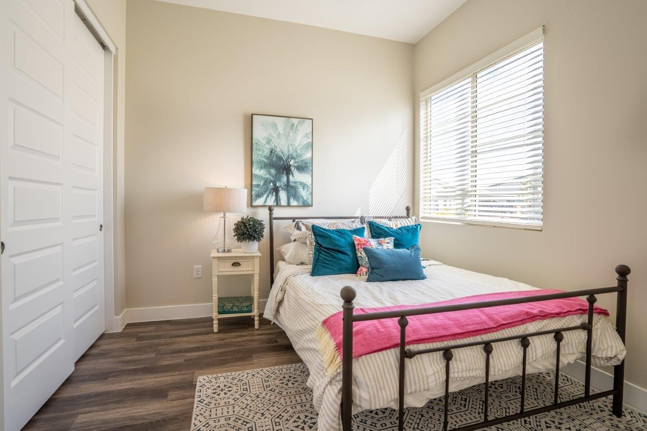 A large bed with a nightstand sits in a bedroom with double closet doors and a window at Village Greens of Queen Creek
