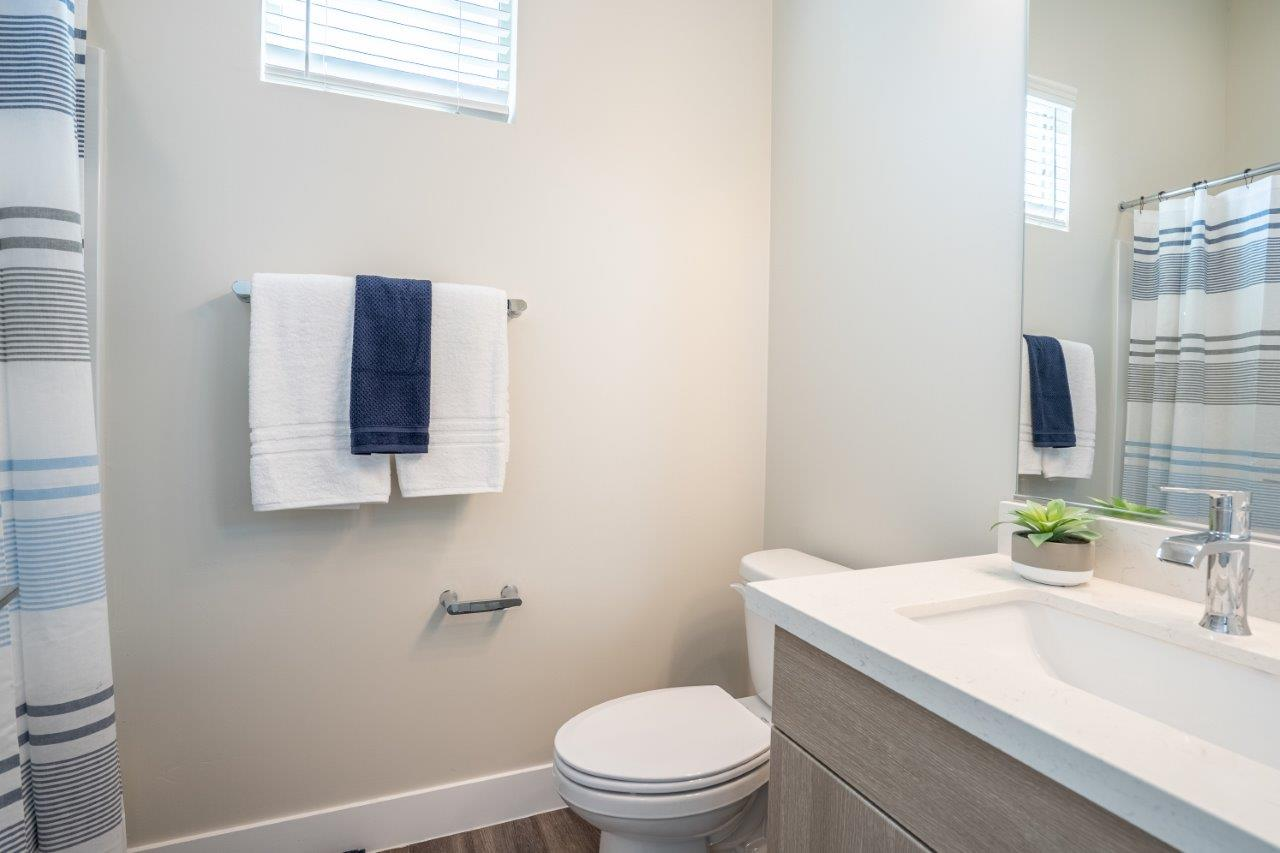 Model bathroom with a toilet and mirrored vanity sink with storage in an apartment at Village Greens of Queen Creek