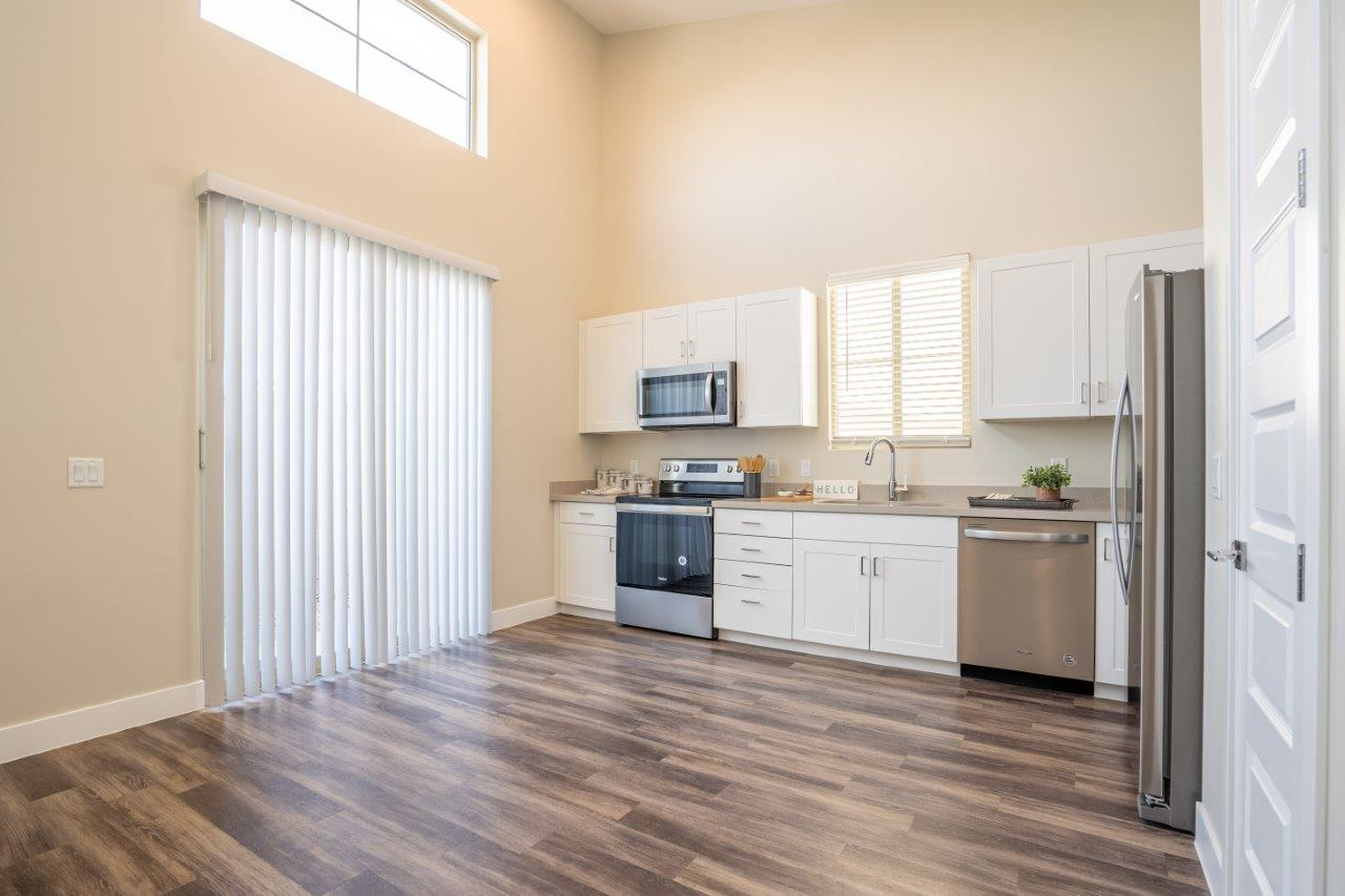 Model kitchen at Village Green of Queen Creek with wood-style flooring, modern appliances and a sliding glass door