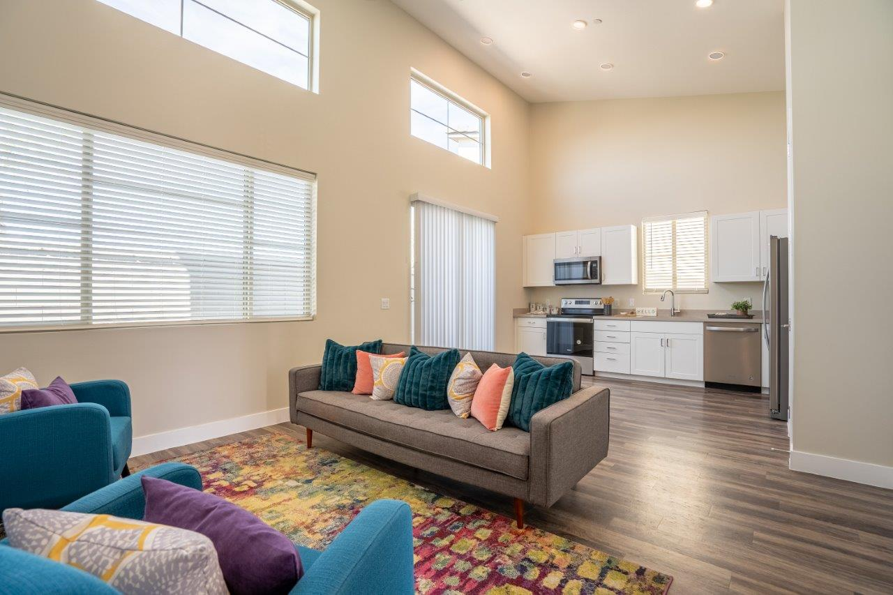 Furnished open floor plan living area has a couch and chairs in an apartment at Village Green of Queen Creek
