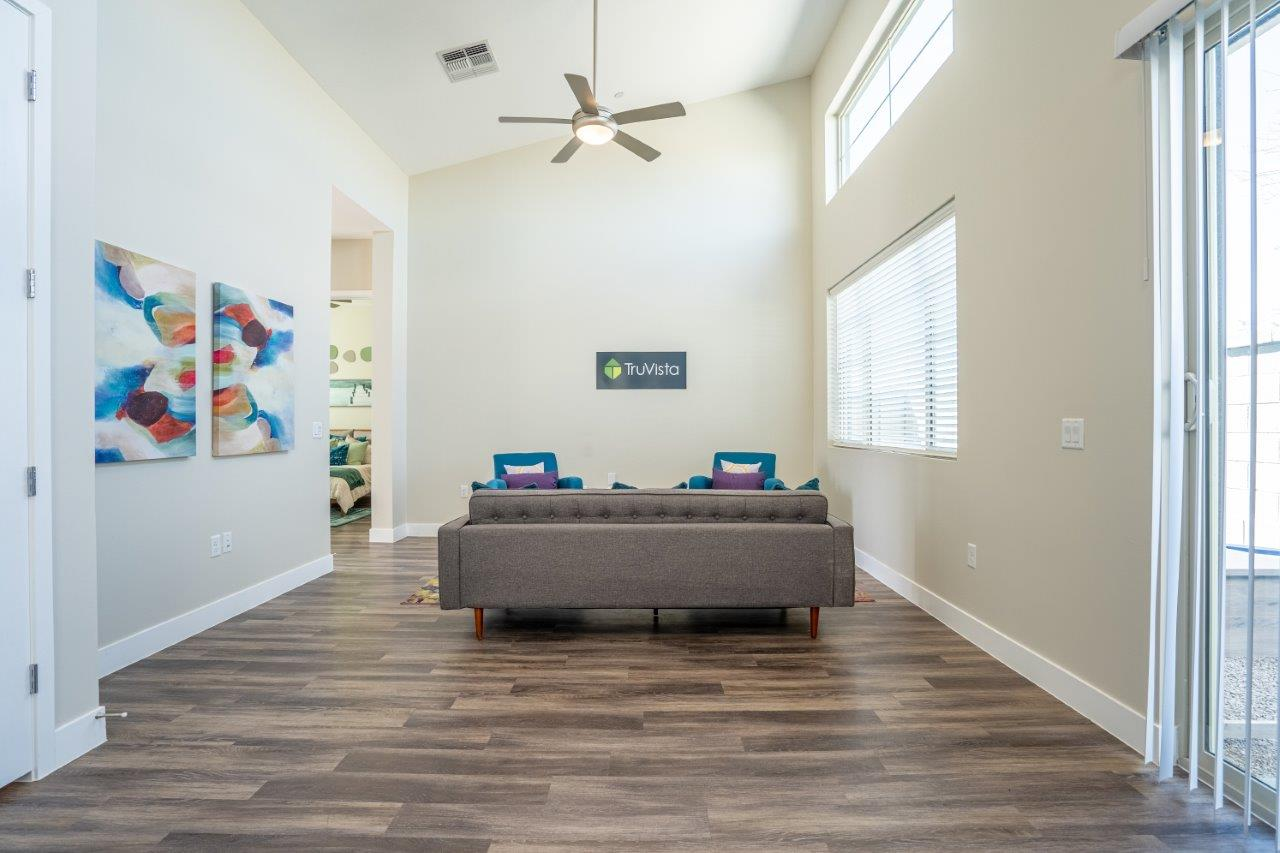 Wood-style flooring in a living room furnished with a couch at Village Greens of Queen Creek
