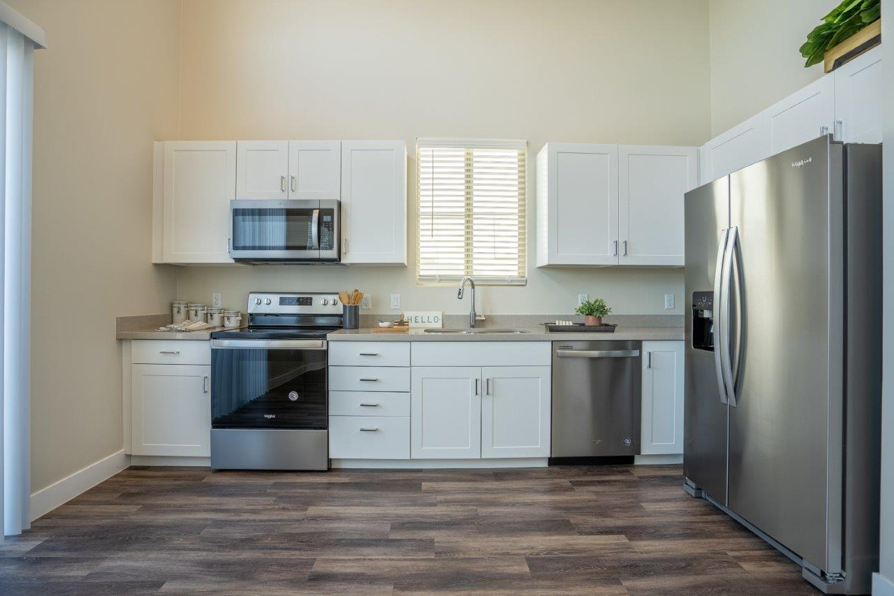 A kitchen with wood-style flooring and stainless steel appliances in an apartment at Village Greens of Queen Creek