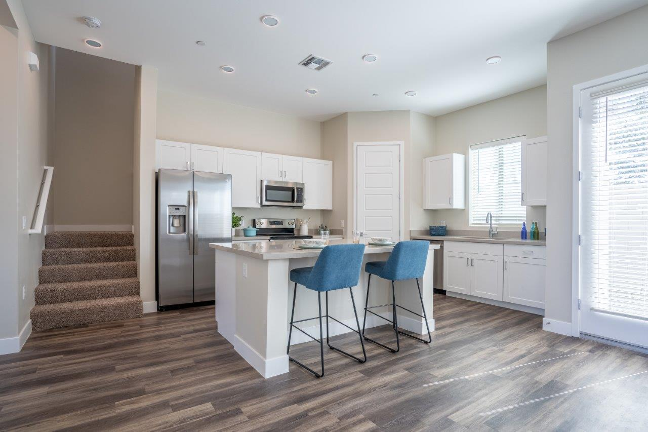 An open concept kitchen has an island with two stools in an apartment at Village Greens of Queen Creek