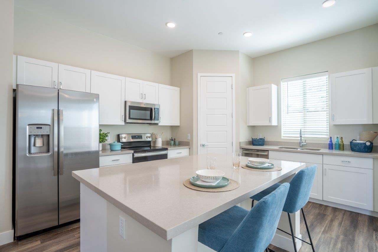 An island with 2 stools sits in the middle of a kitchen with stainless steel appliances at Village Greens of Queen Creek