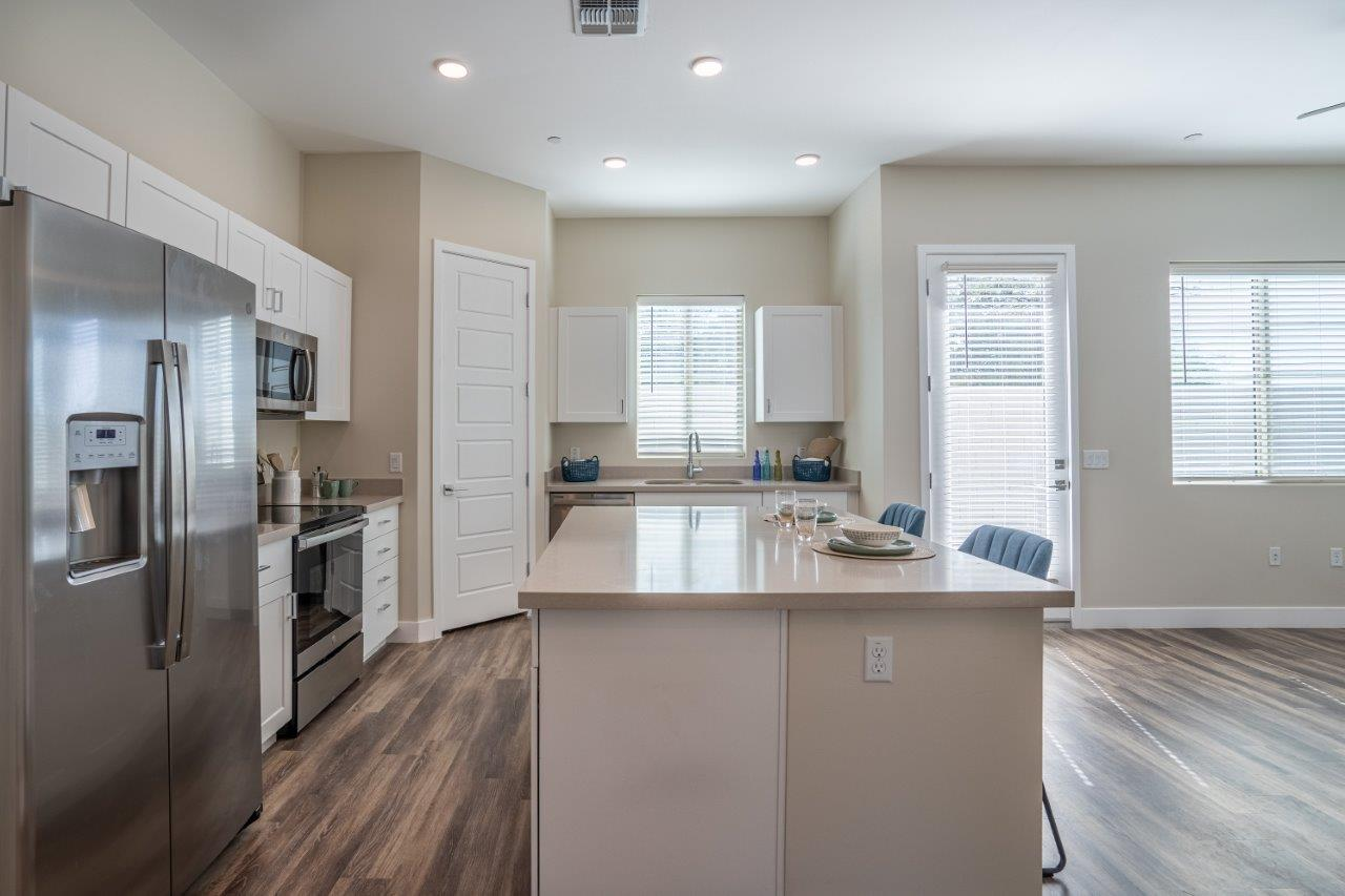 Open floor plan shows a kitchen with a large island in an apartment at Village Greens of Queen Creek