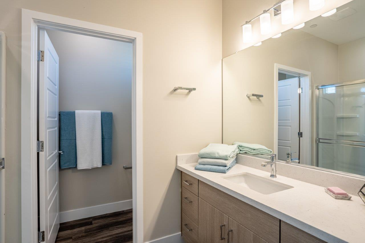 Model bathroom has a long mirrored vanity sink with storage in an apartment at Village Greens of Queen Creek