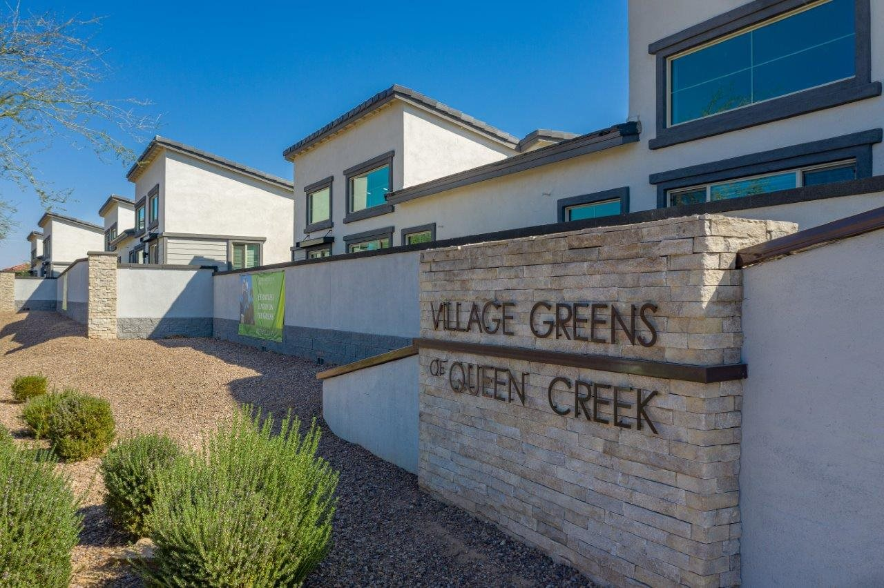 """Landscaped wall along the property with a sign """"Village Green of Queen Creek"""""""