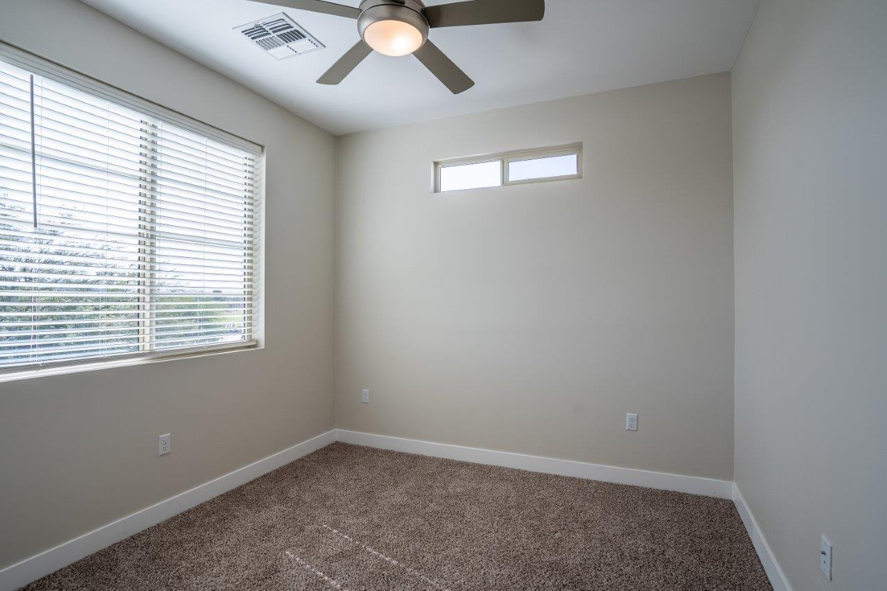 A carpeted bedroom has a window and ceiling fan in an apartment at Village Greens of Queen Creek