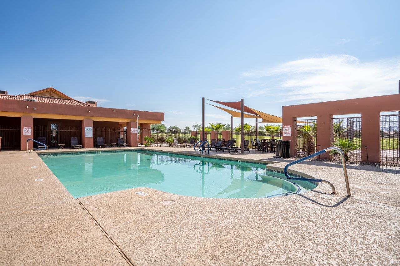 The pool is surrounded by a sundeck with lounge chairs at Village Greens of Queen Creek