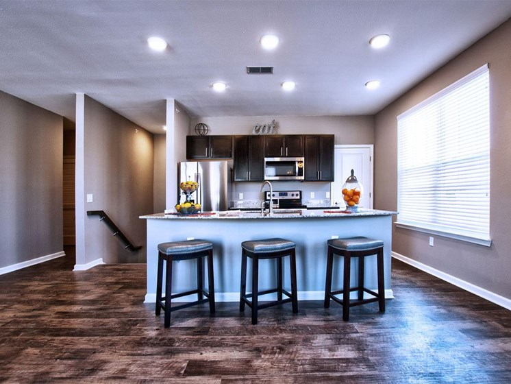 Apartments in Goshen - Stylish Kitchen With Granite Breakfast Bar, Dark Wood Cabinets, and Stainless Steel Appliances
