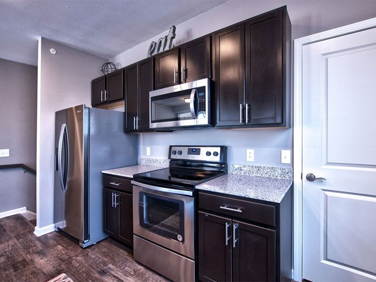 Apartments in Goshen - kitchen with dark wood cabinetry and stainless steel appliances