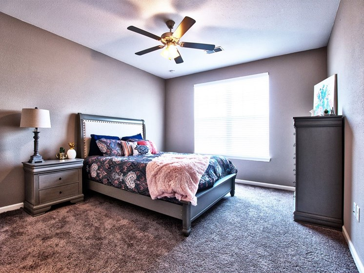 Goshen Apartments - Spacious Bedroom With Cozy Gray Carpet, Large Window, and Ceiling Fan