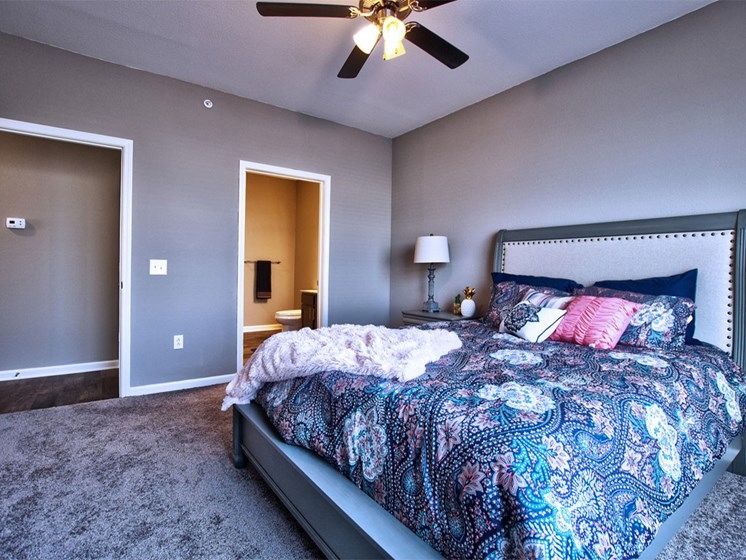 Goshen apartments - large bedroom with ceiling fan and carpet flooring