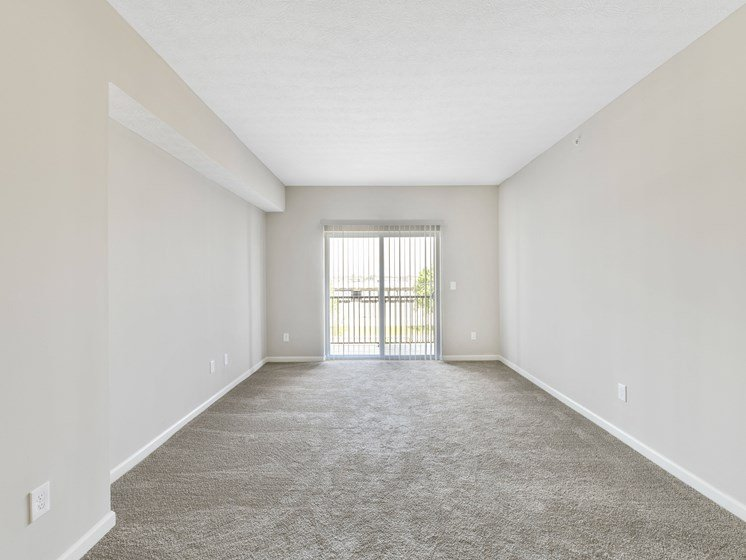 Living Room with Door Access to Balcony at Austin Place Apartments