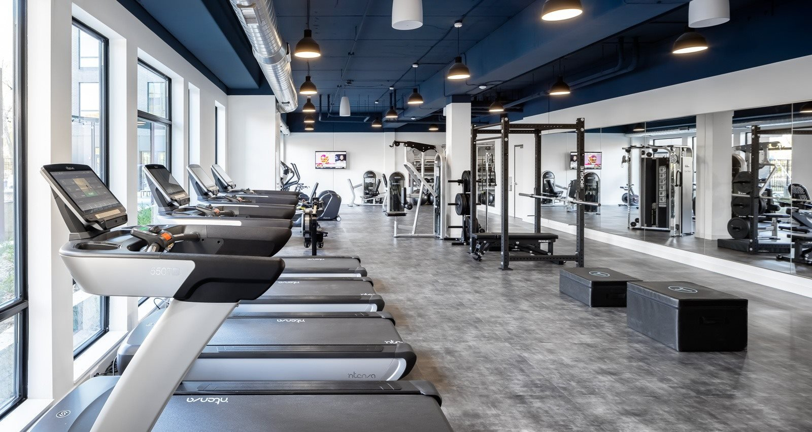 Treadmills and mirror in forefront of gym for apartment residents