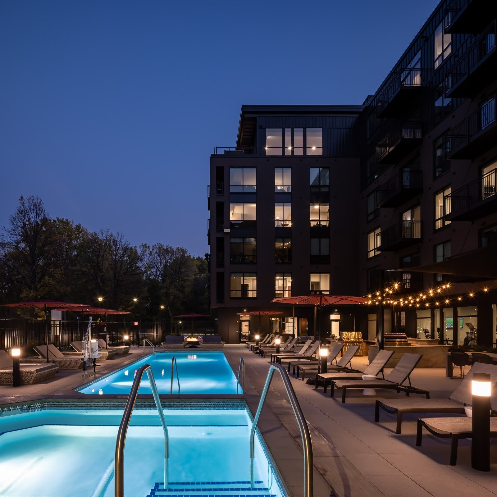 Dusk view of hot tub, pool, and pool seating on terrace with lit apartment windows