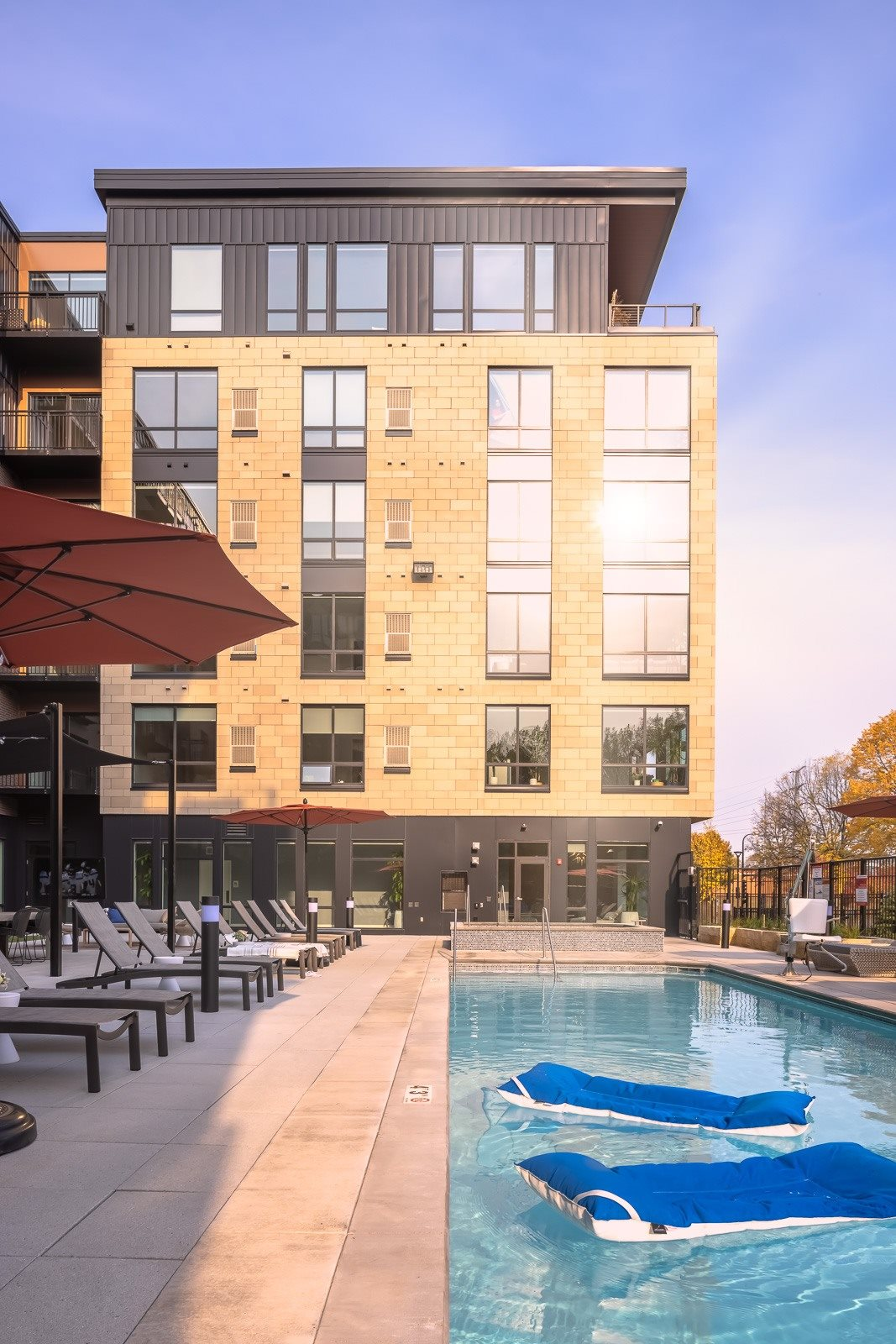 Outdoor heated pool on terrace with sunshine reflecting off windows
