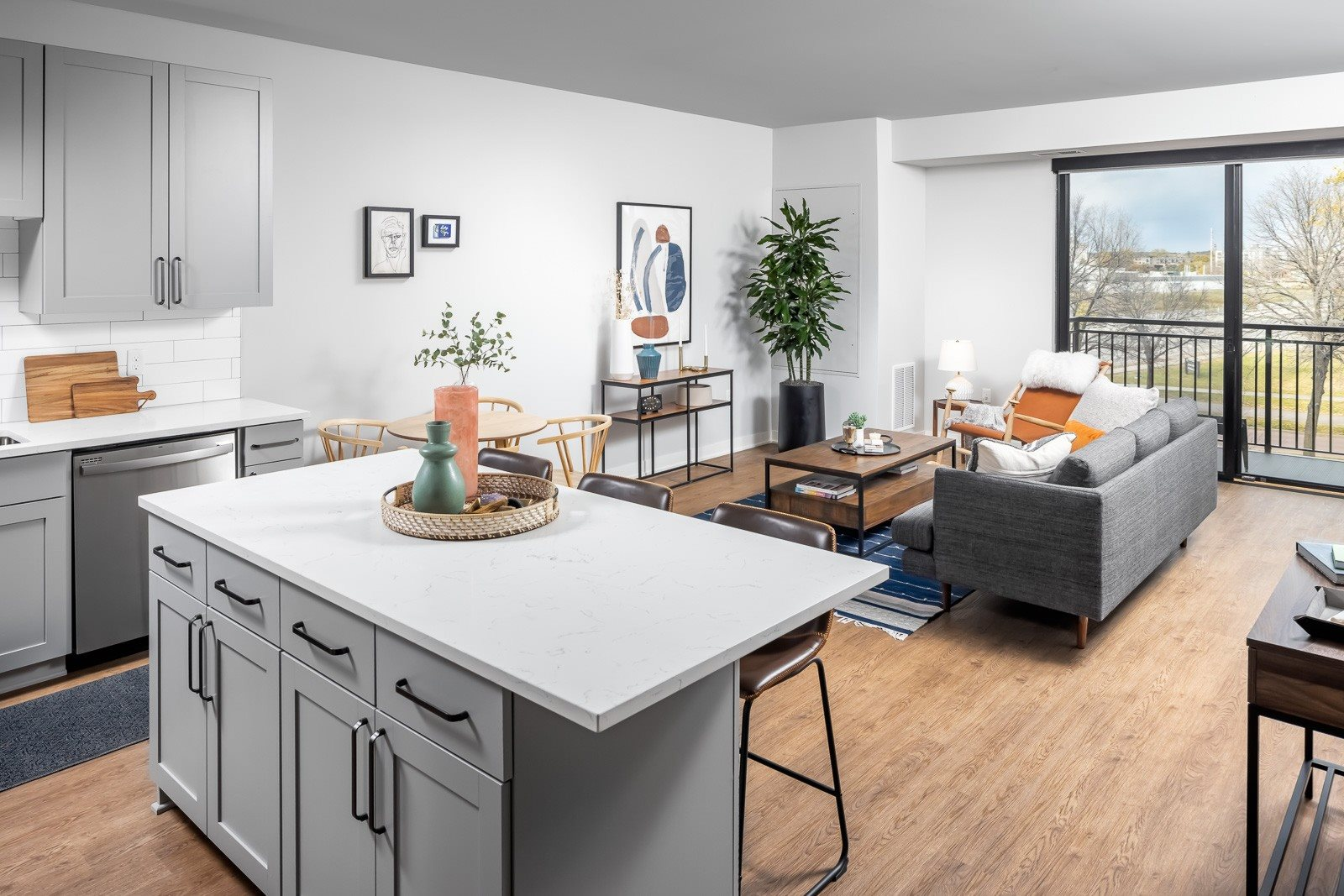 Kitchen island and living room with balcony in one bedroom apartment
