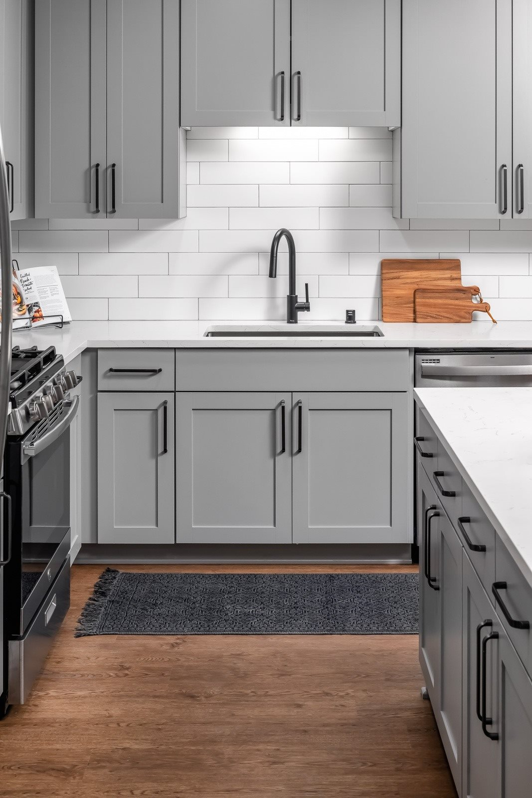 Designer finishes in kitchen with black cabinet pulls and shaker style cabinets