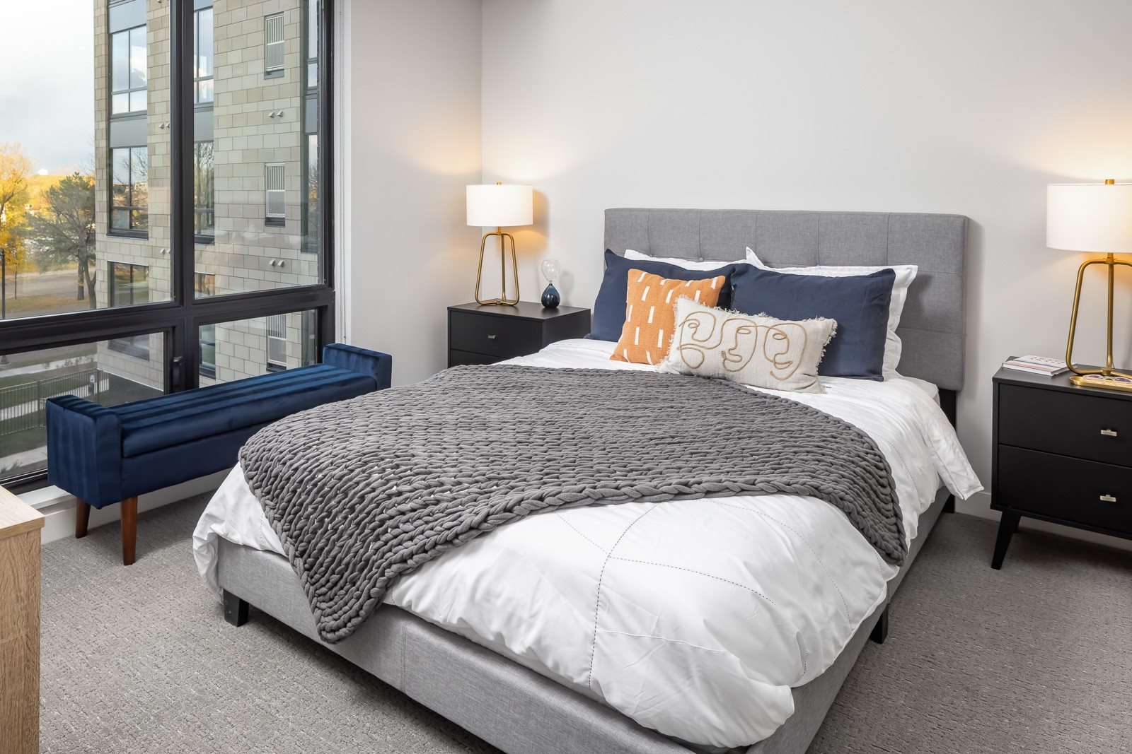 Spacious bedroom with large windows overlooking river in one bedroom apartment