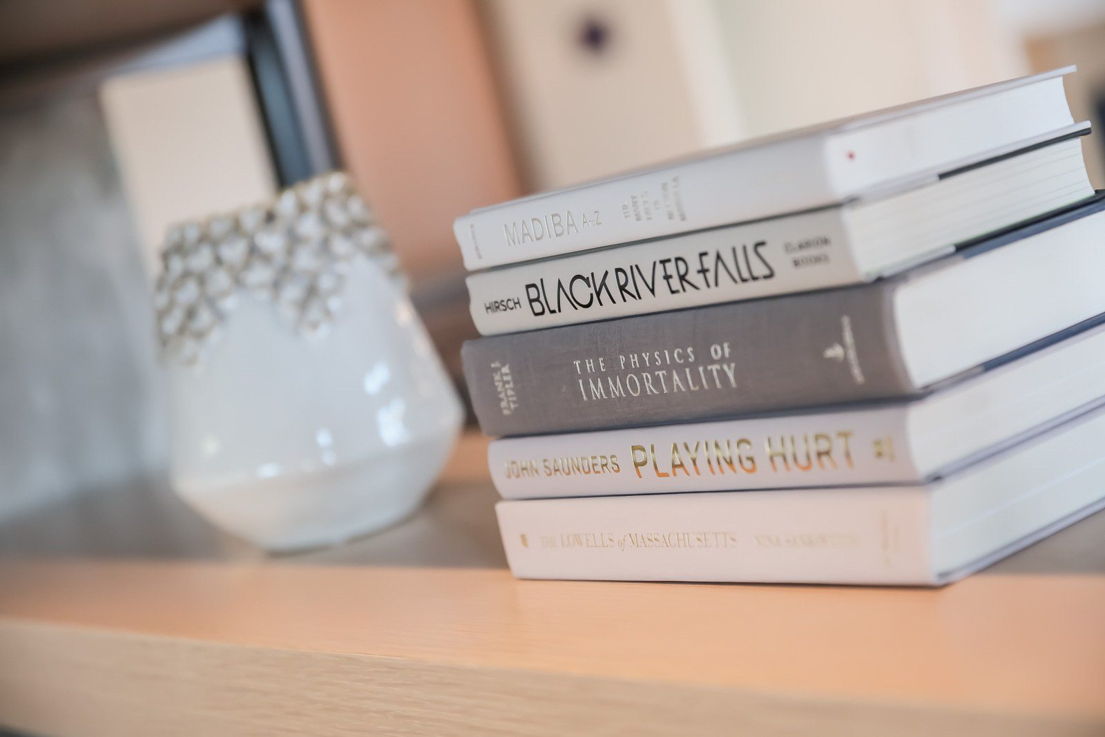 Bookshelf decor with curated white books and vase in lobby