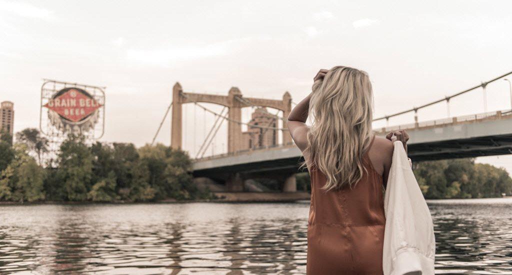 woman outlooking bridge over river