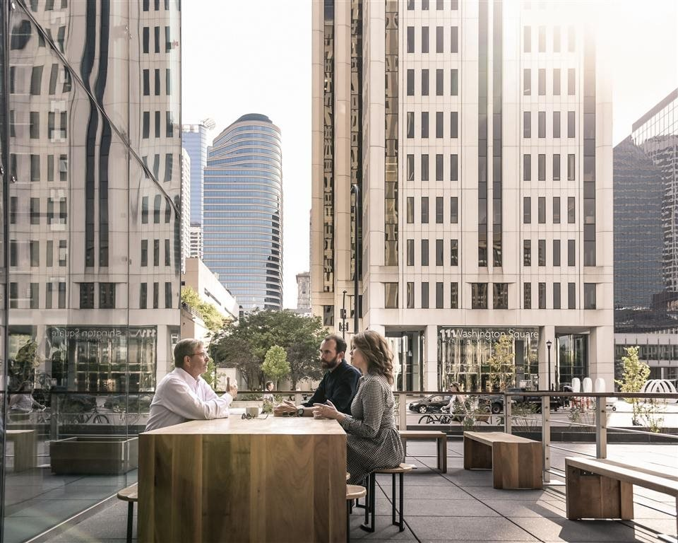 people eating outside on a table in the city