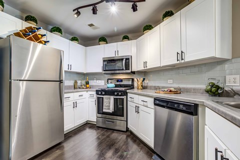 Kitchen with stainless steel appliances, white cabinets and hardwood floors