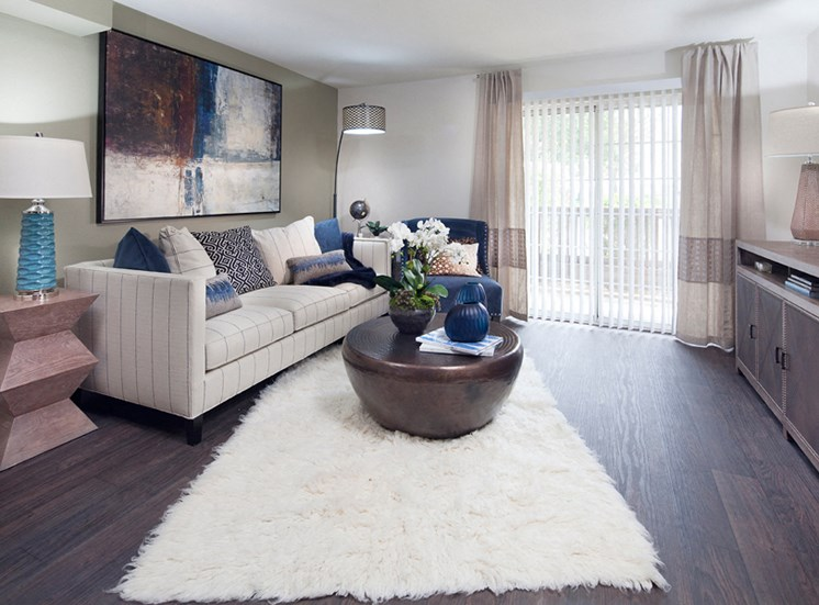 Ardenne Apartment living room with white rug, couch and sliding glass doors to outside