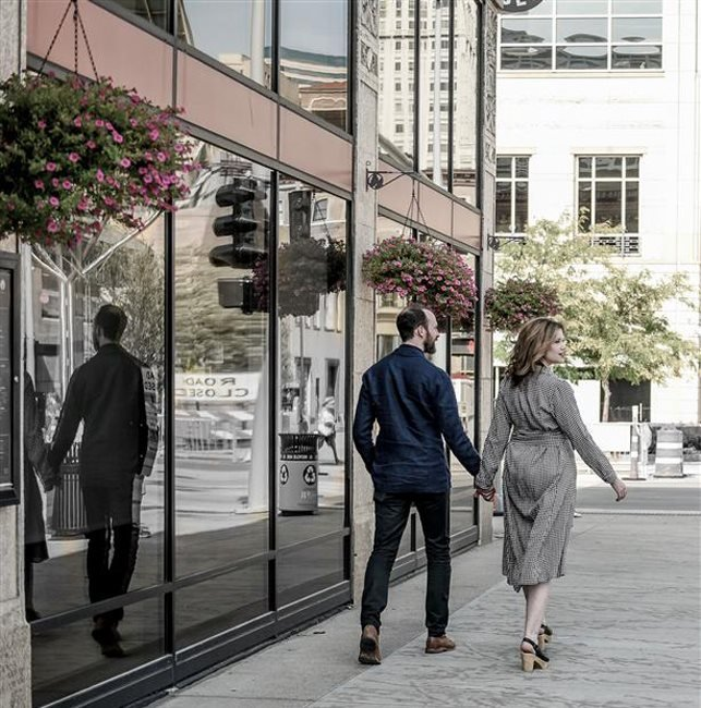 man and woman holding hands walking down street