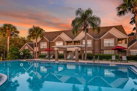 Bloomingdale Woods Apartments Valrico Florida Building Exteriors with Pool in Foreground, and Mature Palm Trees, with Sunset in background