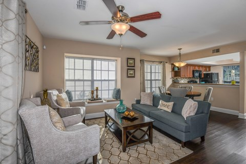 Bloomingdale Woods Apartments Valrico Florida Model Apartment Living Room Area with Couch and 2 Lounge Chairs and Ceiling Fan with View towards Kitchen and Eat-In area with dining table and chairs