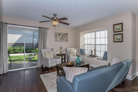 Bloomingdale Woods Apartments Valrico Florida Model Apartment Living Room with Couch and Lounge Chairs with View of Walkout Patio and Ceiling Fan