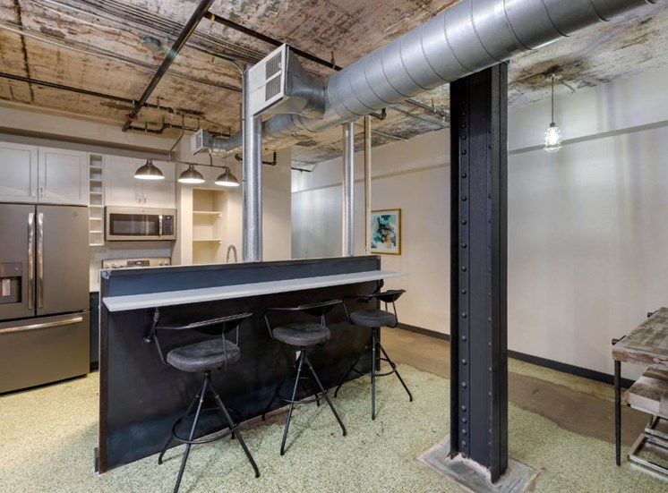 Industrial Style Apartment wit Exposed Concrete and Ducts, Kitchen with Breakfast Bar with Stools and White Cabinets Around Stainless Steel Appliances