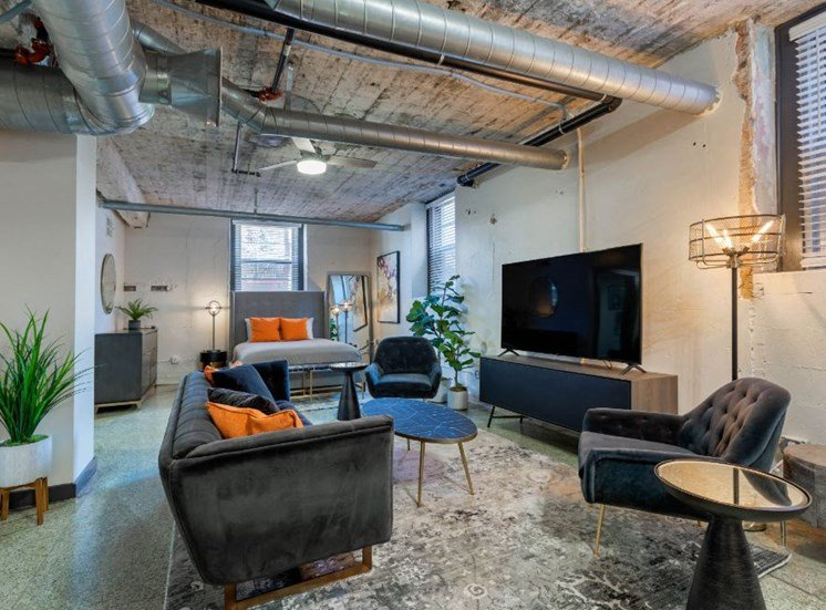 Industrial Style Apartment Living Room with Exposed Ducts and Concrete, Windows, Contemporary Couch, Armchair, Coffee Table, Side Table and Entertainment Center Under TV with Bed Area and Bed in the Background