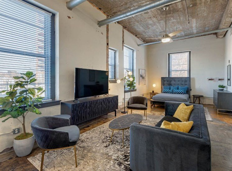 Industrial Style Apartment Living Room with Exposed Ducts and Concrete, Windows, Contemporary Couch, Armchair, Coffee Table, Side Table and Entertainment Center Under TV with Bed in the Background